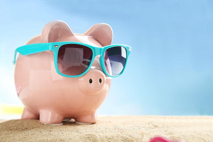 piggy bank in sunglasses on a beach
