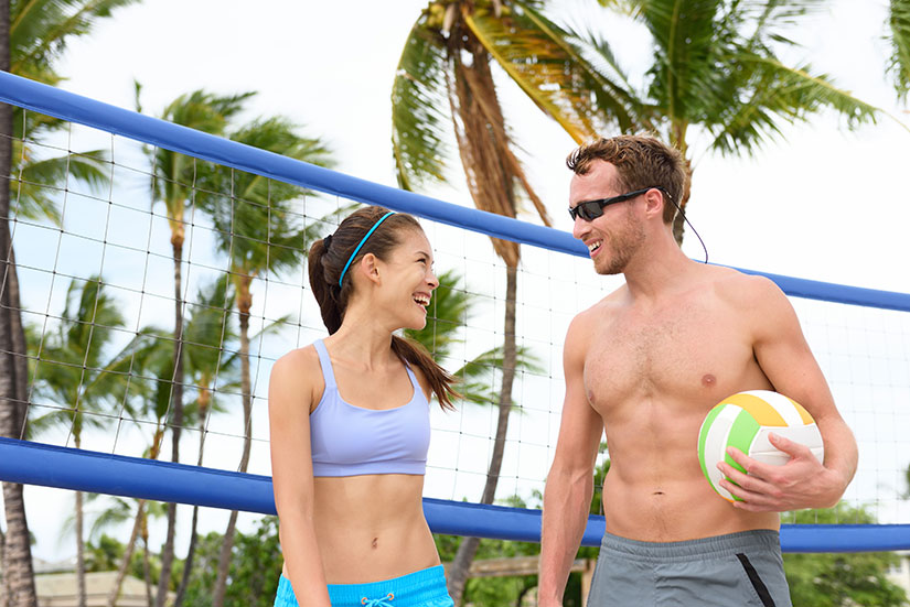couple in sunglasses playing beach volleyball